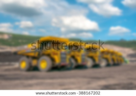 blurred background - fleet big yellow loading truck in open pit mine under cloudy blue sky - stock photo