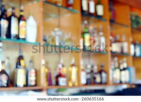 Blurred background image of bar back with shelves of liquor bottles. - stock photo