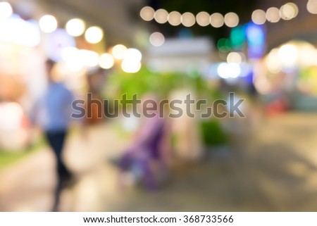 blurred background night market on street decorated with festive lights. - stock photo