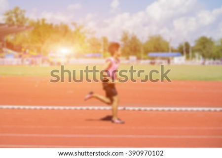 Blurred background of  a man running a race,on the running track,vintage color. - stock photo