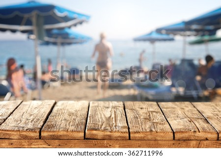 blurred background of beach umbrellas and closeup of table and woman  - stock photo