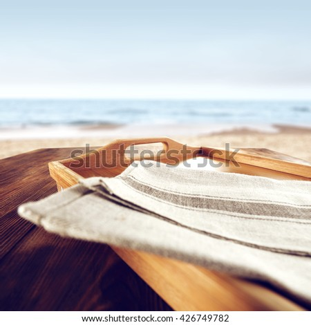 blurred background of blue sea and tray and gray napkin on wooden old table place