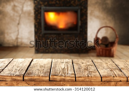 blurred background of fireplace and shabby wooden old table for your decoration