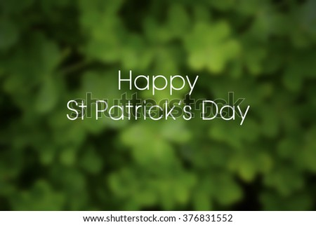 Blurred background of green shamrock clover for St Patricks Day, with sample greeting text.  - stock photo