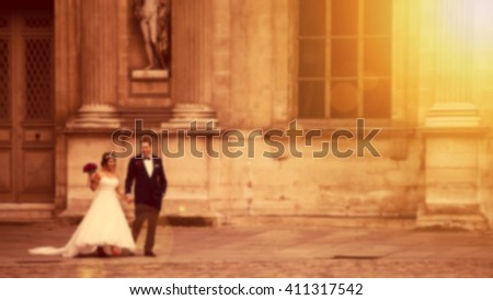 Blurred background of groom and bride in the sunset - stock photo
