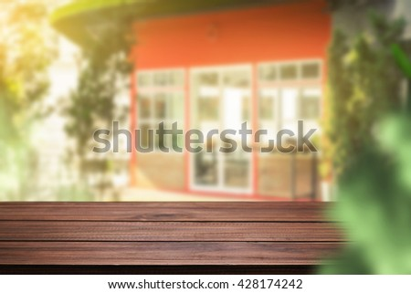 Blurred background of home garden and wooden table free space for product display. - stock photo