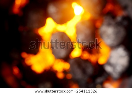 Blurred background of hot glowing coals and charcoal in a fire or on a portable barbecue, full frame - stock photo