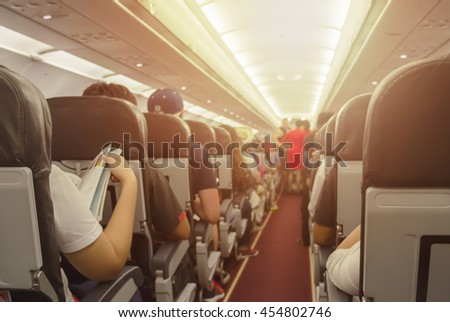 Blurred background of interior aircraft , flight attendant helping passenger to put luggage cabin compartment. - stock photo