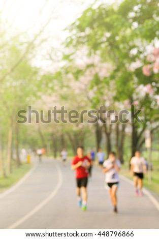 Blurred background of park with running people