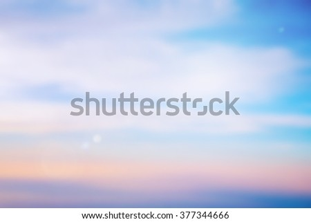 blurred background of sky sea with lens flare light.blurry nature backdrop concept:vintage film effect tone color.early morning canopy heaven concept:blur white soft clouds with shining sparkle flash - stock photo