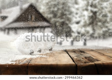 blurred background of snow and forest with table of three white balls  - stock photo