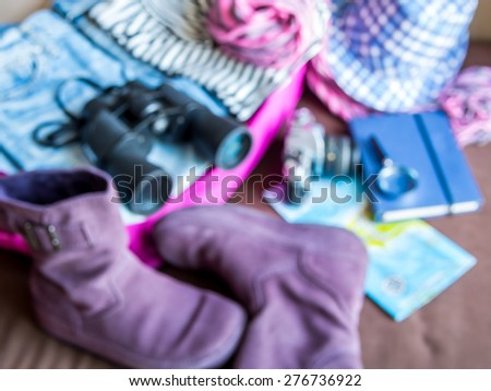 Blurred background of summer holiday luggage stuff scattered on bed / traveling concept