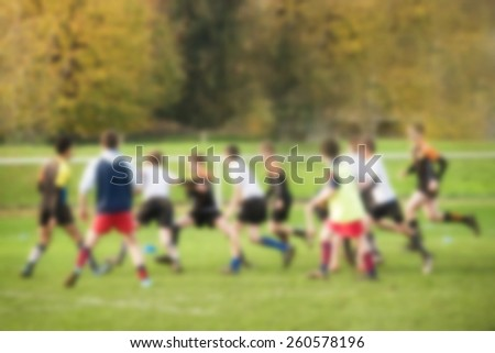 Blurred background of unidentified boys playing a team sport game, outdoor - stock photo