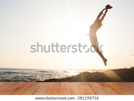 Blurred background of woman jumping in sunset - stock photo