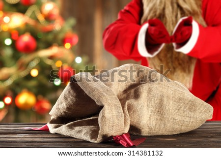 blurred background of xmas tree in home and red santa claus with desk with sack  - stock photo