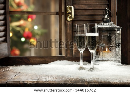 blurred background of xmas tree lights and window of champagne retro lamp and snow and space for your food  - stock photo