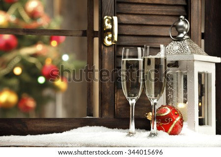 blurred background of xmas tree lights and window of red ball champagne and retro white lamp