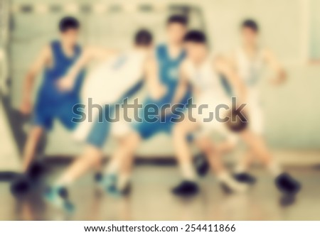 Blurred background, unrecognizable basketball players on the court. Toned photo. - stock photo