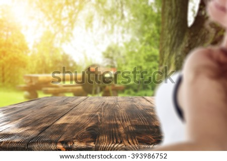 blurred background with young woman and brown old table of free space for you  - stock photo