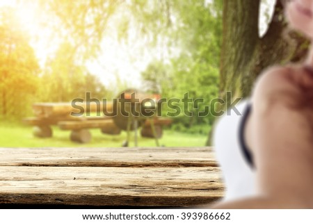 blurred background with young woman and wooden desk and grill and grass  - stock photo