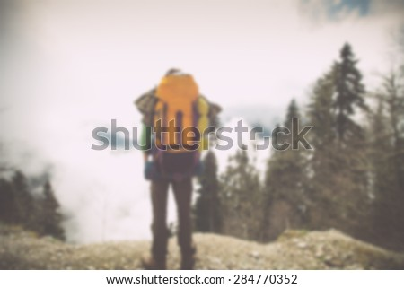 Blurred Background Young Man Traveler with backpack relaxing outdoor Lifestyle hiking concept trendy style rear view - stock photo