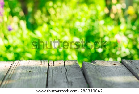 Blurred Backgrounds. Green bokeh in the sunlight, and a wooden table .  - stock photo