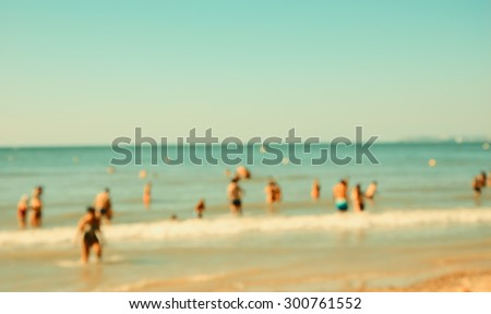 Blurred beach photo with bokeh. People relaxing on beach. Vacation background (Trouville-sur-Mer, Normandy, France) Retro aged photo.  - stock photo