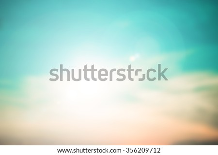 blurred beautiful natural sky landscape background with ray flare lights.blurry sunshine wallpaper concept.backdrop pastel cool tone.idyllic shores sundown hour.abstract dream:glamour teal gold color - stock photo