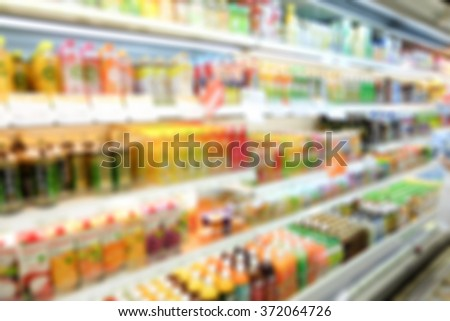 blurred beverage showing on shelves in the cold freezer at department store:blur bottle of drinking water,milk,juice,tea,yogurt background:blurry shopping mall food/drink zone concept:blur supermarket - stock photo