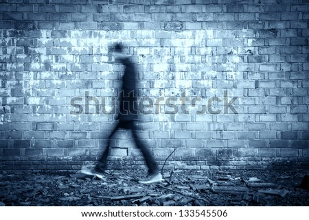 blurred black man walking through a old weathered wall - stock photo