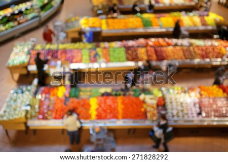 Blurred blurry soft focus background, interior of healthy food store market with fruits and vegetables, people going along the aisles and buying groceries, view from above - stock photo