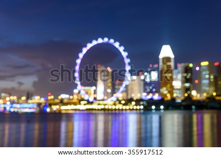 Blurred bokeh abstract motion of Singapore Skylines, Downtown and Financial District buildings reflection along the Singapore River at Blue Hour. Colorful bokeh lights background of Modern City  - stock photo
