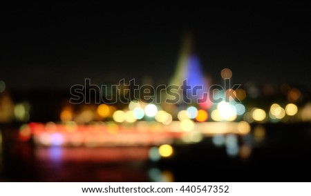 Blurred bokeh background of Wat Arun Temple and boat across Chao Phraya River during sunset in Bangkok, Thailand - stock photo
