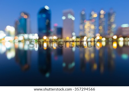 Blurred bokeh waterfront city office building during twilight - stock photo