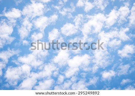 Blurred bright blue sky with soft puffy scattered clouds moving in the air : Holiday summer sky with natural soft fluffy clouds  - stock photo