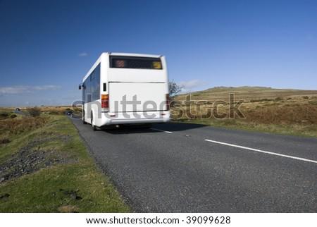 Blurred bus on rural road. Dartmoor, Devon, UK - stock photo