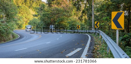 Blurred car on the countryside road with warning curve road sign - stock photo