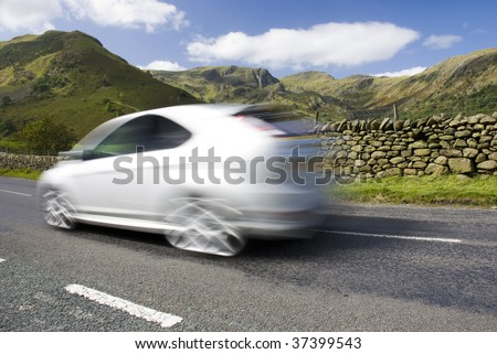 Blurred car on the mountain road, Lake District National Park, Cumbria, UK - stock photo