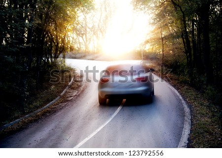 blurred car trip in sunny forest road - stock photo