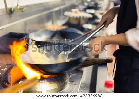blurred chef of a restaurant kitchen, motion cooking, take a photo low speed shutter - stock photo