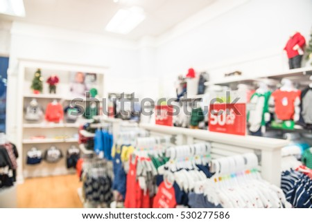 Blurred children clothing store with discount sign and variety of clothes for newborn, kids, toddlers, babies. Colorful shirts, trousers, pants, blouses, bodysuits arranged on shelves and hangers.