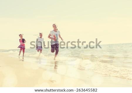 Blurred children running on the beach, focus on sand in foreground. Instagram effect - stock photo