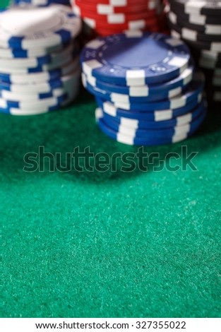 blurred chips for poker on green playing table with place for text - stock photo