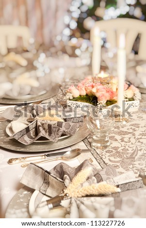 Blurred christmas tree and fancy dinner table - stock photo