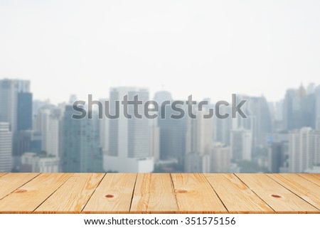blurred city in sunny day backgrounds with old vintage wooden desk tabletop: put and show your products on display or wallpaper  - stock photo
