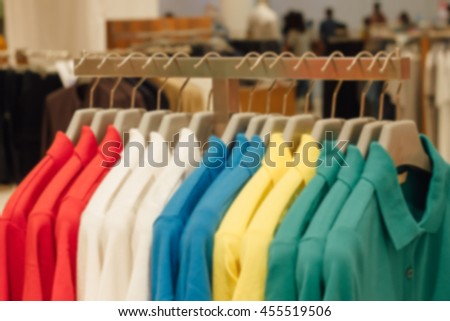 Blurred Clothing Store concept : abstract of blurred hanging red, white, blue, yellow and green shirts on hanger in clothing store for sale : beauty and fashion and business concept - stock photo