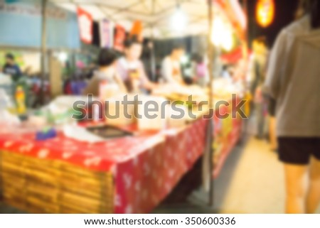 blurred colorful background from night walking street with people walking and shopping.