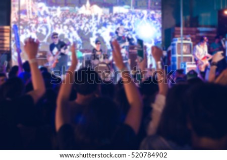 blurred crowd of fans cheering at night concert