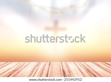 Blurred crown of thorns and the cross on sunset background and wooden paving. - stock photo