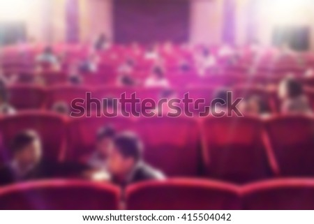 Blurred dark background. Cinema with empty comfortable red seats and projector. The atmosphere in the theater before the Movies start.